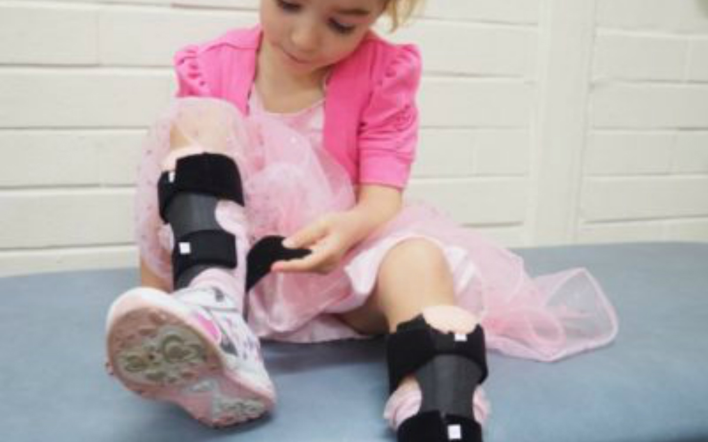Young girl in pink dress, sitting down and putting on her ankle foot orthotic