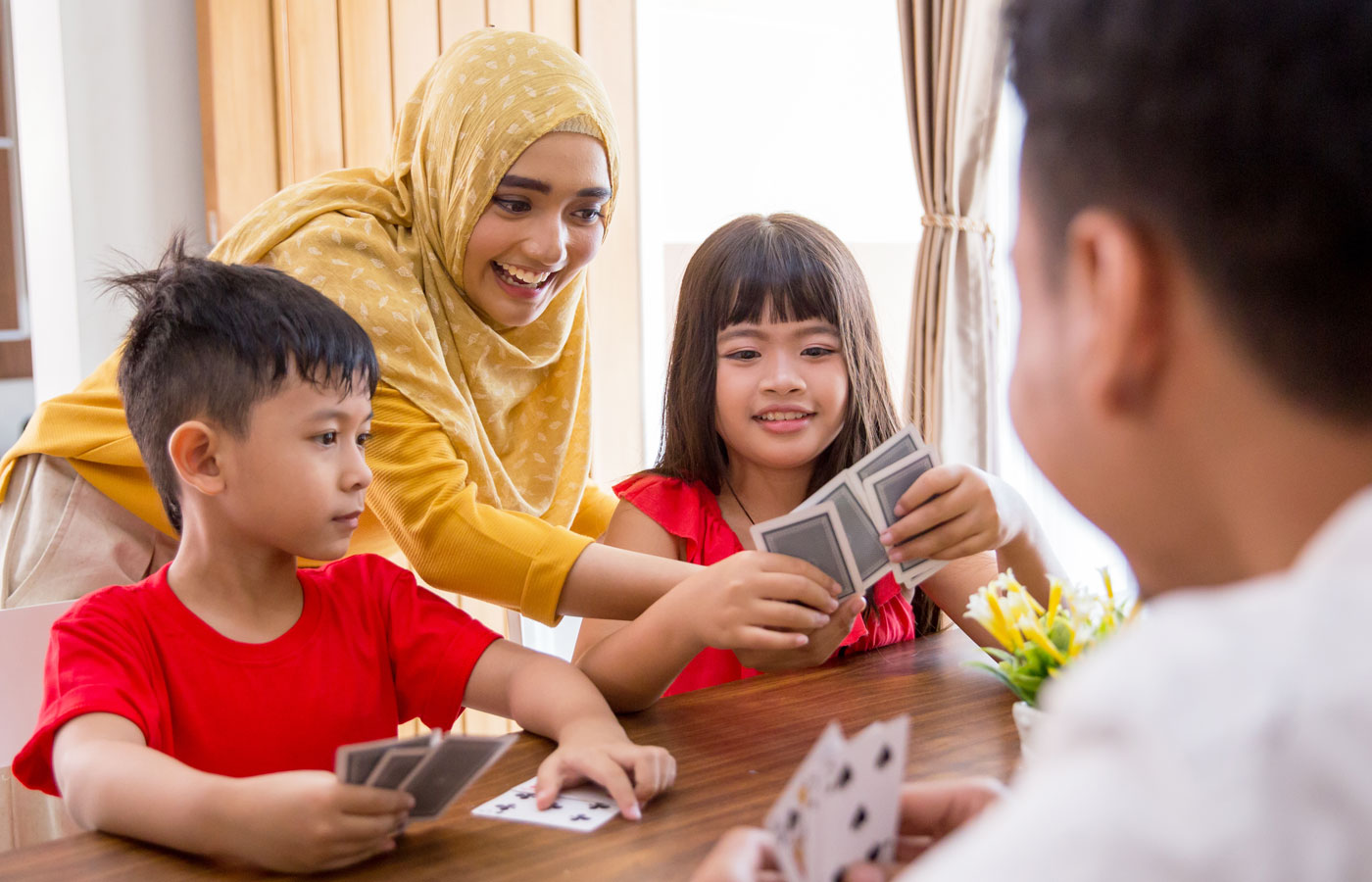 Mother and Father with Young Children playing card games