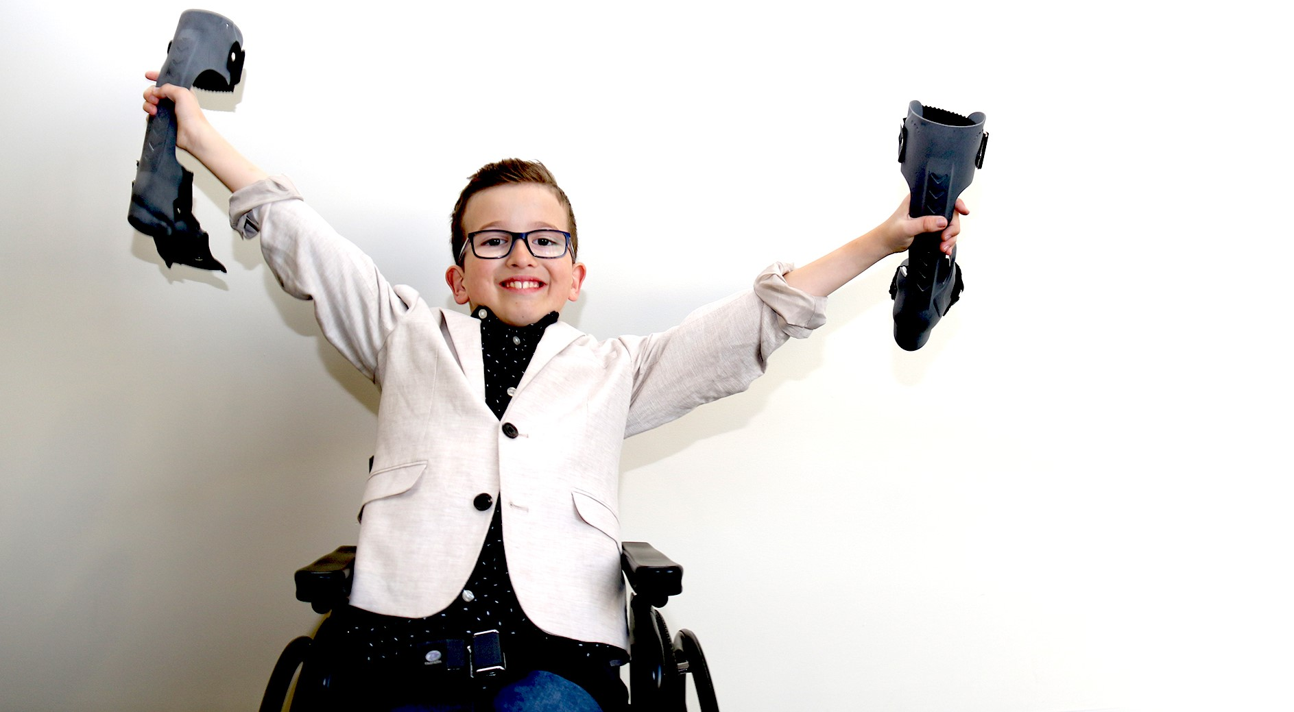 Young boy in wheelchair holding two orthotics