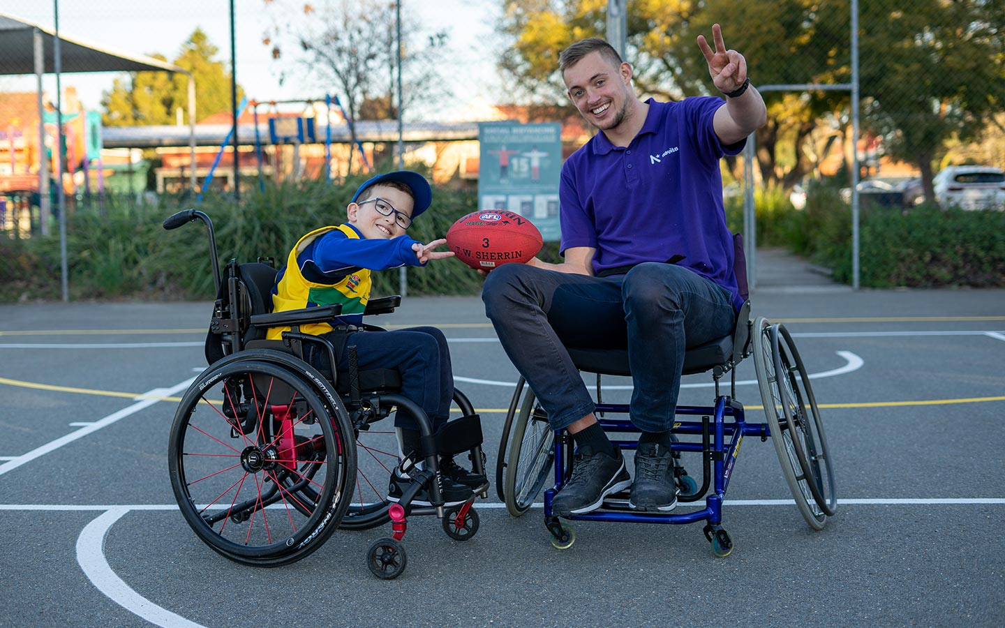 Young boy and man in wheelchairs, with the man holding a football